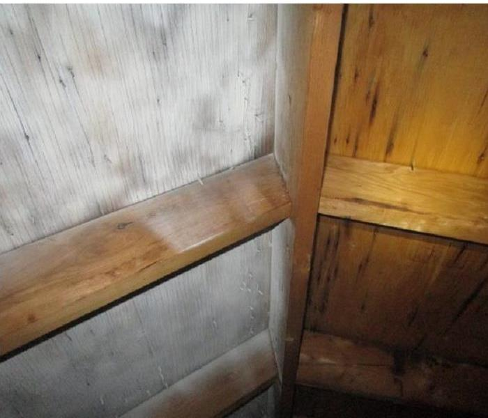 Attic ceiling with clean wood sheathing and white sealer sprayed on