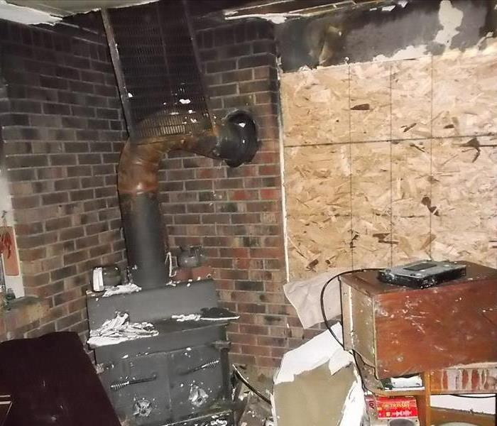 Inside of home with charred woodburning stove and boarded up wall