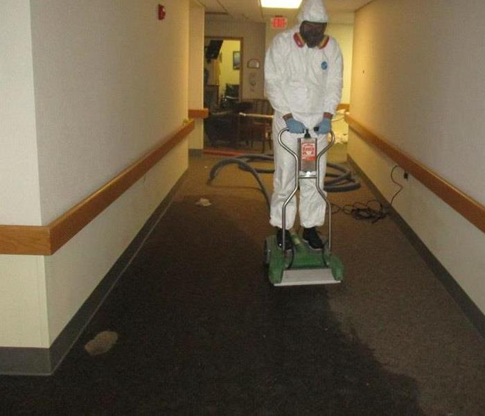 SERVPRO tech wearing a respirator and full PPE riding a rover carpet extractor
